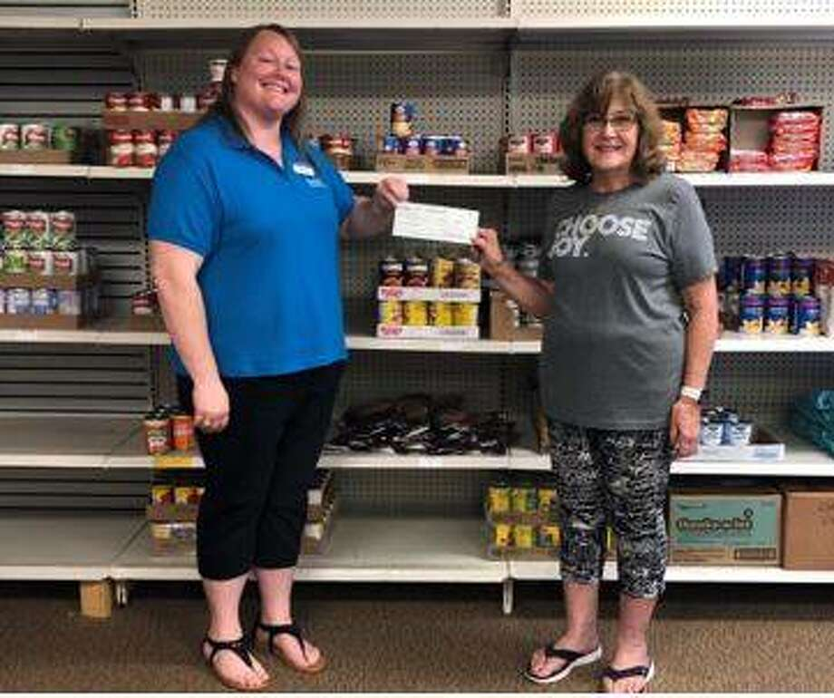 Staunton Branch Manager Casey Bridges of Bank of Hillsboro, left, presents Mount Olive Care Center Director Nancy Hubert with a $2,500 donation..