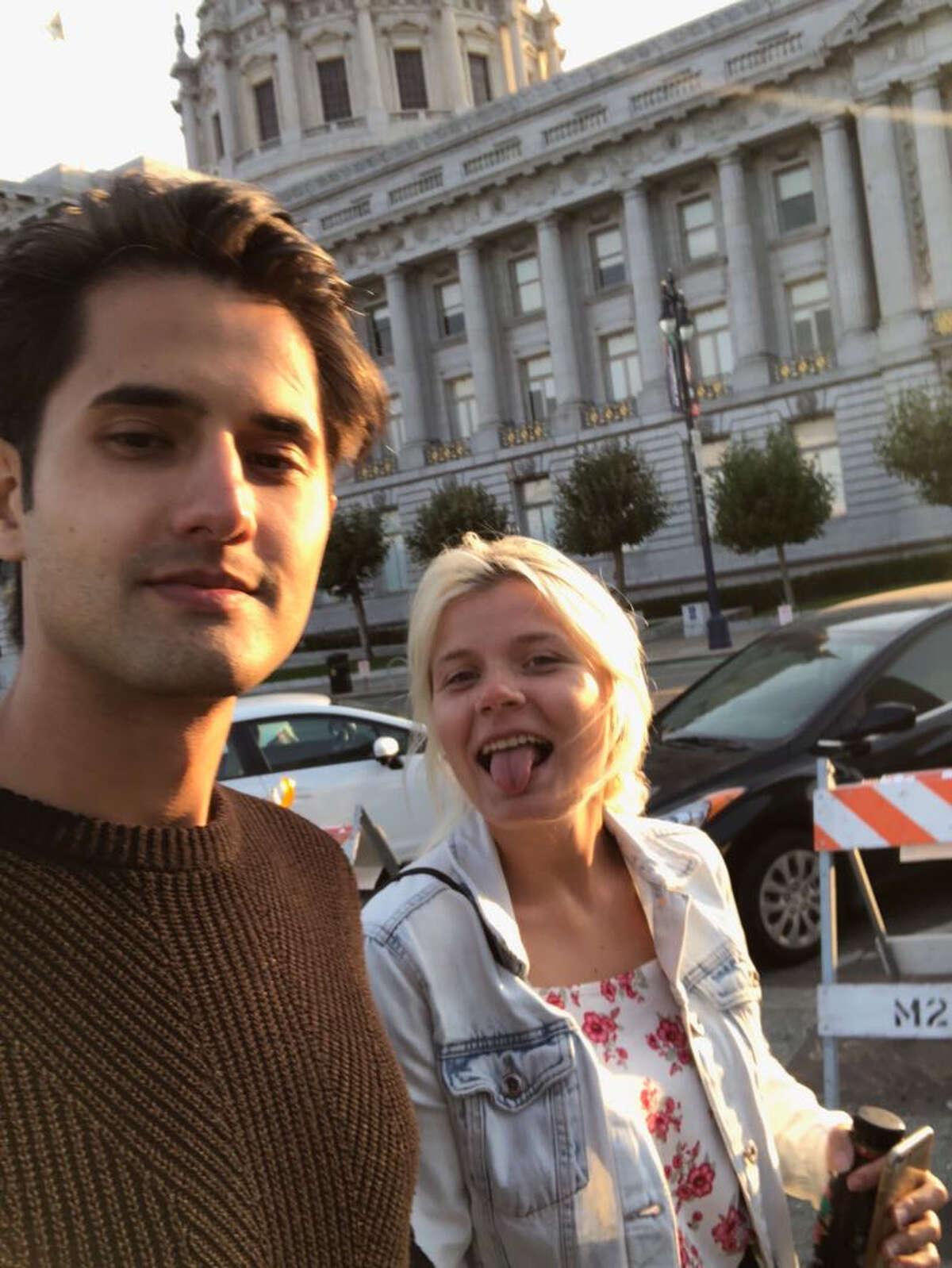 Saskia Talvio and Serdar Serttop pose for a selfie as they walk by San Francisco City Hall.