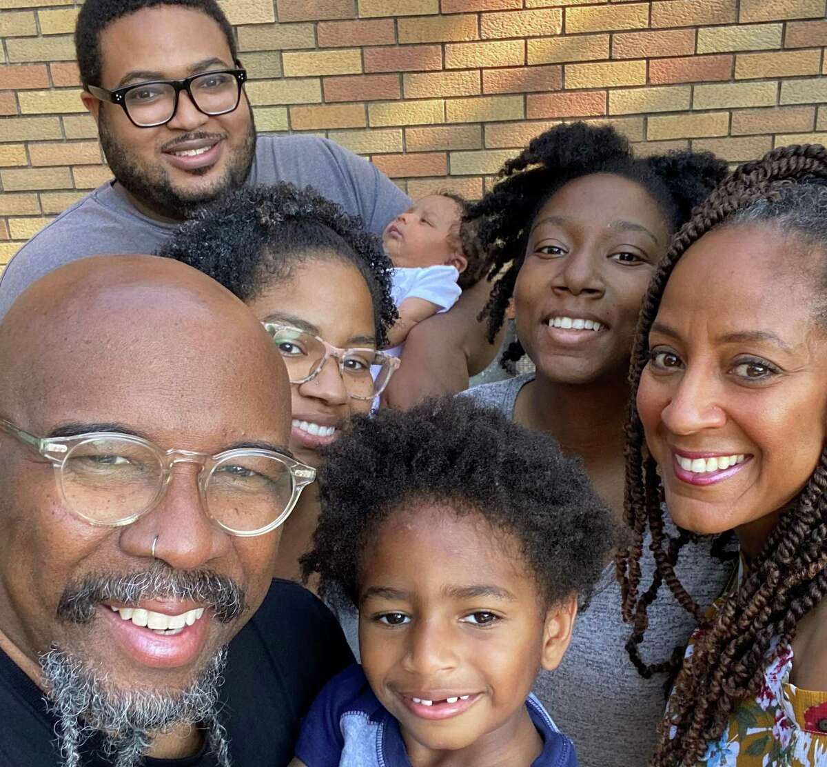 """St. John's Downtown pastors Juanita Campbell Rasmus, right, and husband Rudy are surrounded by their family. In her new book, """"Learning to Be: Finding Your Center After the Bottom Falls Out"""" (InterVarsity Press, $21.99), Rasmus chronicles her own mental """"crash"""" in 1999."""