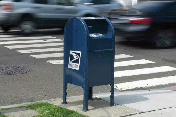 Cars pass by a USPS mailbox along the Post Road in central Greenwich, Conn. Monday, Aug. 17, 2020.