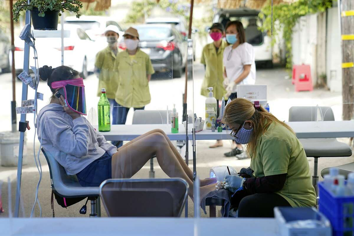 FILE - In this July 22, 2020, file photo, Tyson Salomon, left, gets a pedicure outside Pampered Hands nail salon in Los Angeles. Dr. Mark Ghaly, the state health secretary, said nail salons could also reopen with restrictions. The livelihoods of tens of thousands of mostly minority women hang in the balance as the coronavirus pandemic continues to affect the nail industry. (AP Photo/Ashley Landis, File)