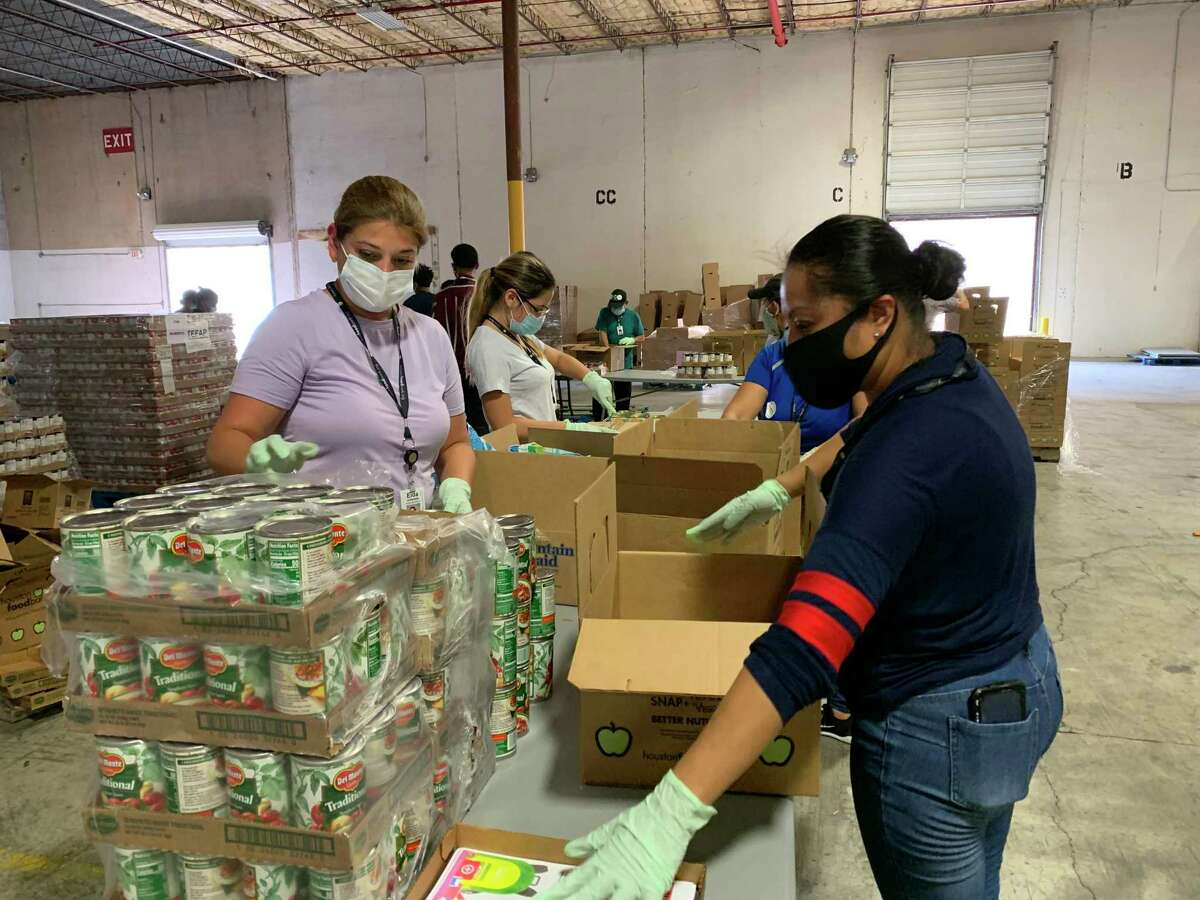 Volunteers pack food boxes for distribution during the pandemic at the Houston Food Bank.
