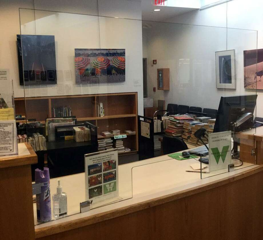 Wilton Library is opening its building to patrons for in-person express service appointments only beginning Monday, Sept. 28. Pictured: The library's reconfigured circulation desk with protective glass shields for patron and staff safety. Photo: Kathy Trentos Photo