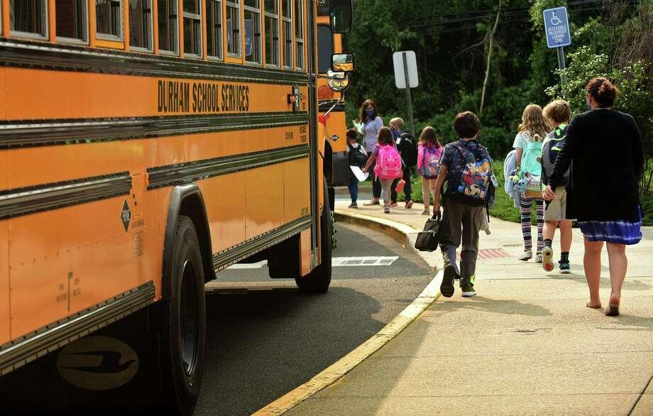 School staff help students boarding buses at Fox Run Elementary School Thursday, September 16, 2020. Photo: Erik Trautmann / Hearst Connecticut Media / Norwalk Hour