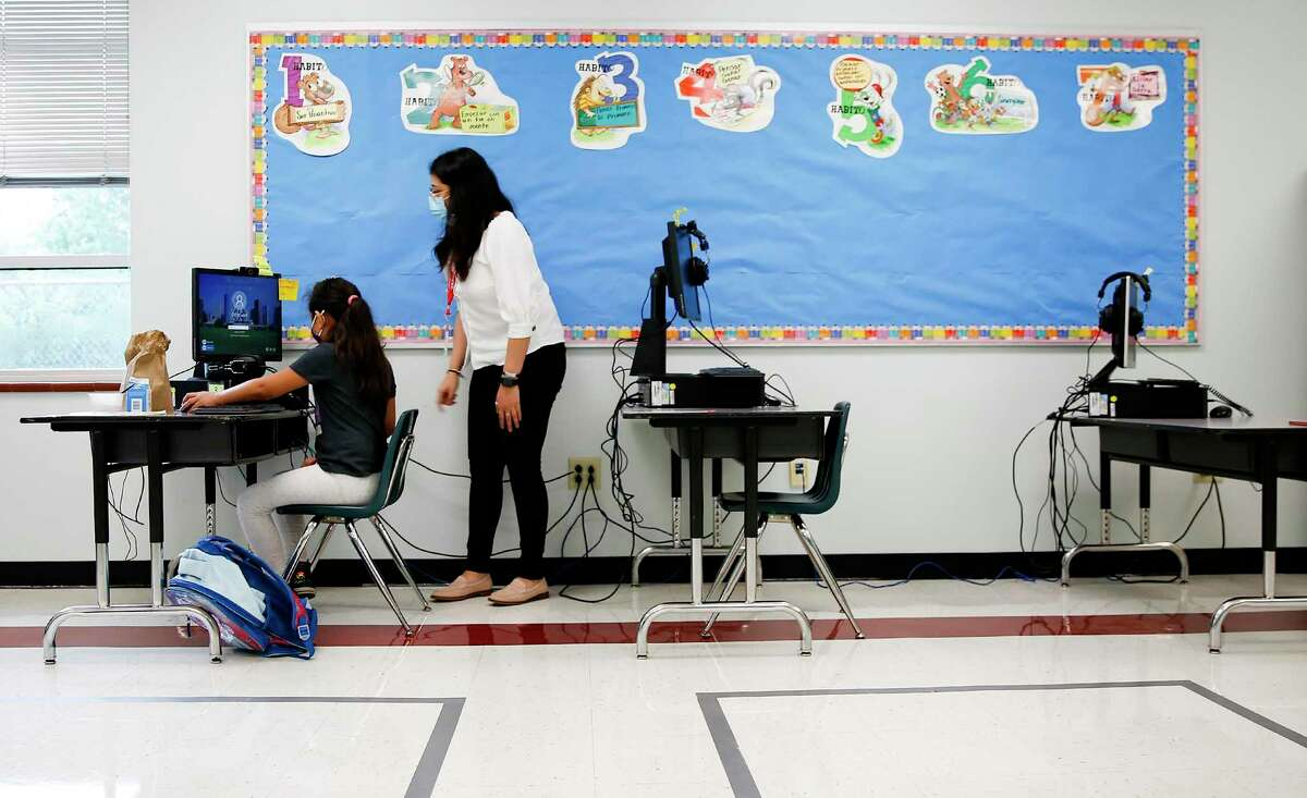 Houston ISD teaching assistant Selena Calderon, pictured in September, helps a second-grader student as she tries to log on for the first day of school at Seguin Elementary School. Families have until Friday to decide whether to send their children to HISD campuses for in-person instruction or take classes online.