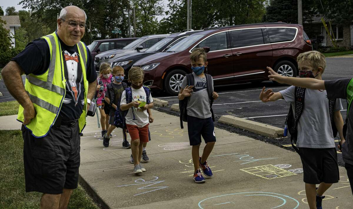 Bo Jarabak watches Glen Carbon Elementary students wave and wish him a happy retirement after dismissal on Wednesday.