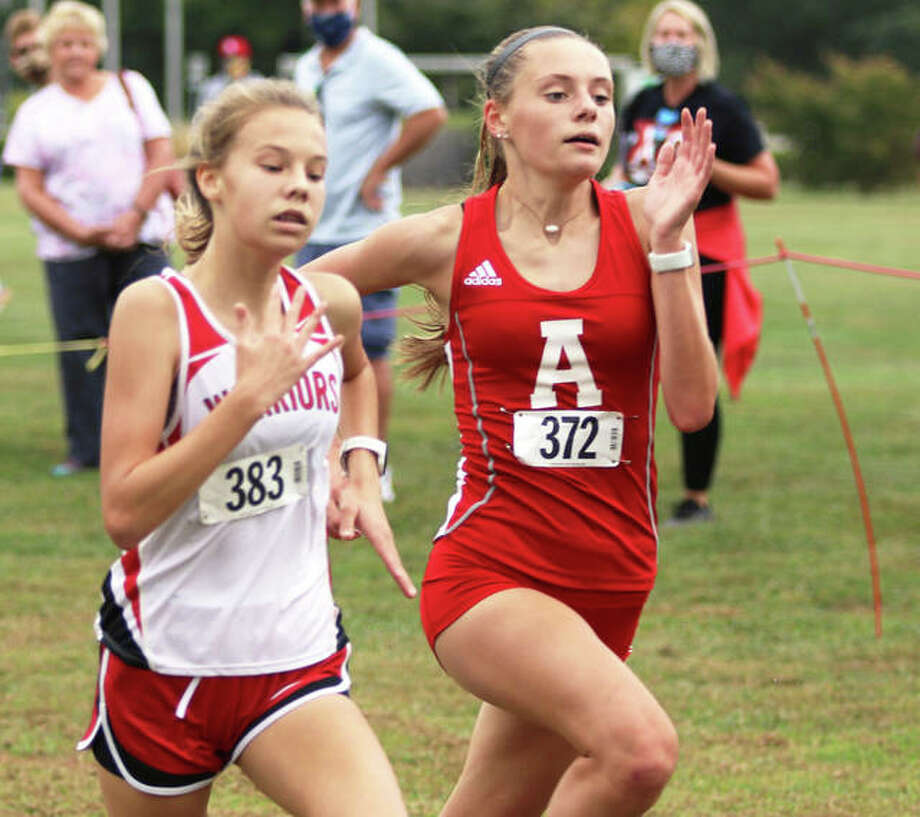 Alton's Alayna Rabozzi (right) overtakes Granite City's Emilee Franklin in the final yards to finish fifth in the girls race at the Alton Invitational cross country meet Wednesday at Moore Park in Alton. Photo: Greg Shashack | The Telegraph