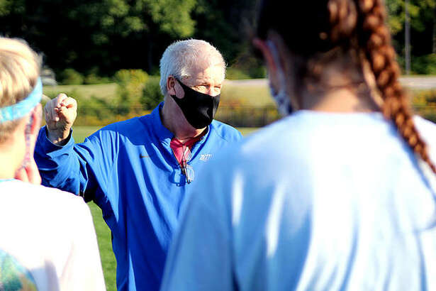 Lewis and Clark Community College women's soccer coach Tim Rooney, wearing a protective face mask, speaks with his players during an early morning practice Thursday at LCCC. It was the team's first off-season practice of the year, since the NJCAA moved the season from fall to spring because of the COVID-19 pandemic.