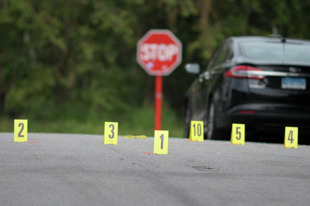 Investigation numbers mark the bullet casings found on Fox St. following a fatal shooting in the Black Rock section of Bridgeport, Conn., Sept. 24, 2020. Police say a man was killed when multiple gunshots were fired into the car his was driving on Fox St. The car then collided with a tree at the corner of Fox St. and Canfield Ave.