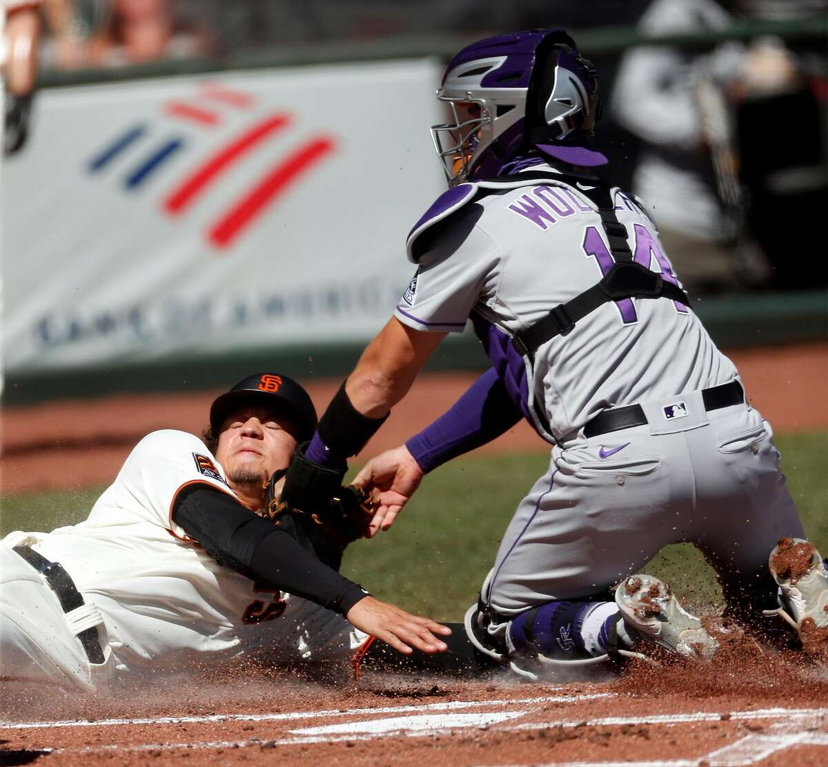 San Francisco Giants' Wilmer Flores is tagged out at home plate by Colorado Rockies' Tony Wolters after an Evan Longoria grounder in 1st inning during MLB game at Oracle Park in San Francisco, Calif., on Thursday, September 24, 2020.