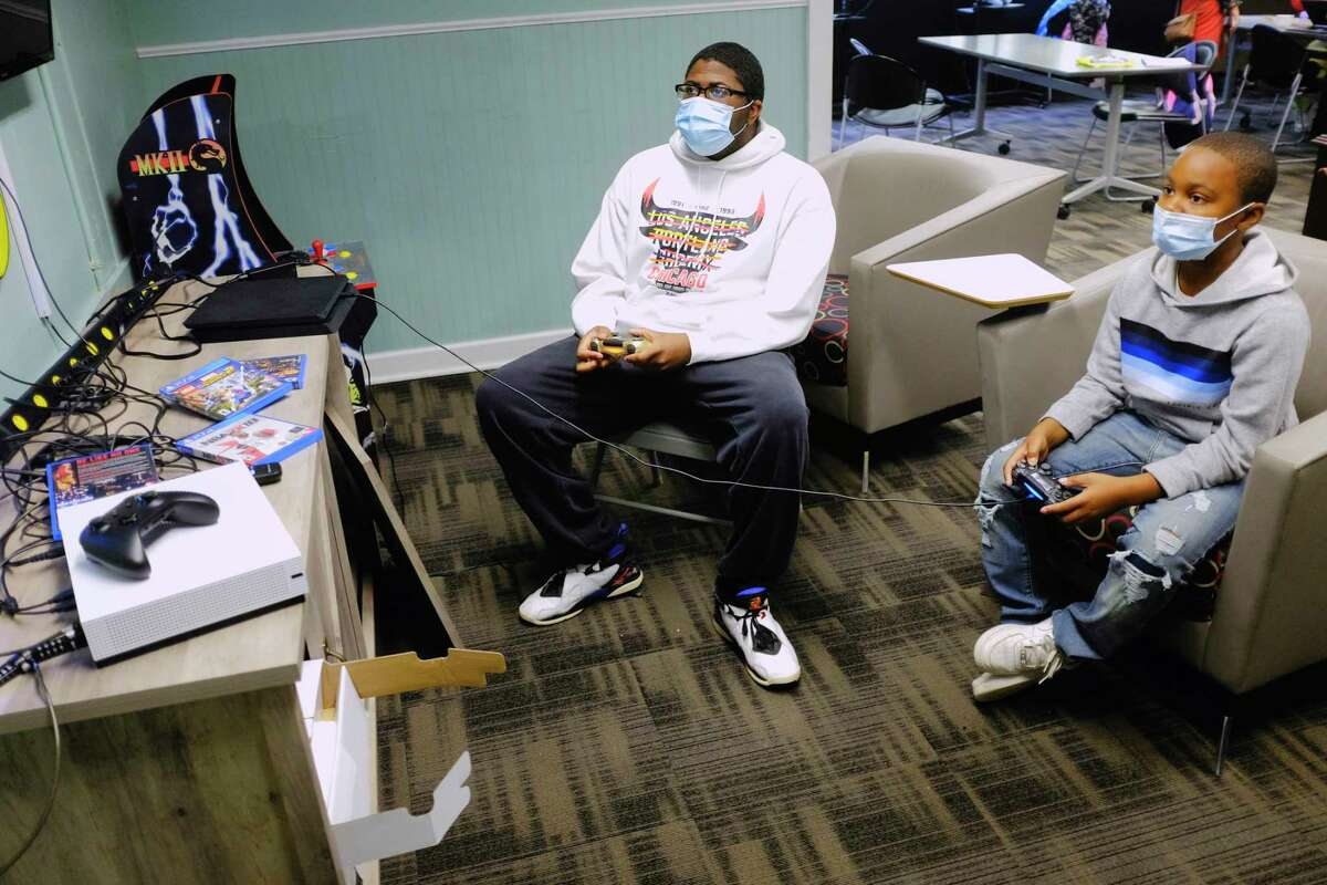 Maurice Williams, left, a teacher/counselor at the Albany Boys & Girls Club, and student Krishna Massey, 10, play a video game during the student's free time on Thursday, Sept. 24, 2020, in Albany, N.Y. (Paul Buckowski/Times Union)