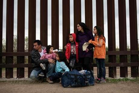 A Honduran family seeking asylum in the United States waits to be taken into custody by Border Patrol officers in Penitas, Texas, Feb. 1, 2019.