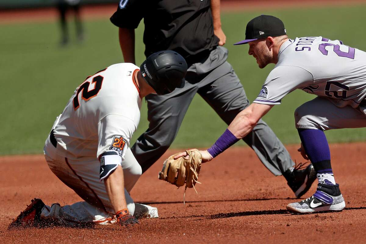San Francisco Giants' Alex Dickerson slides in to second base with a double as Colorado Rockies' Trevor Story applies a late tag in 1st inning during MLB game at Oracle Park in San Francisco, Calif., on Thursday, September 24, 2020.