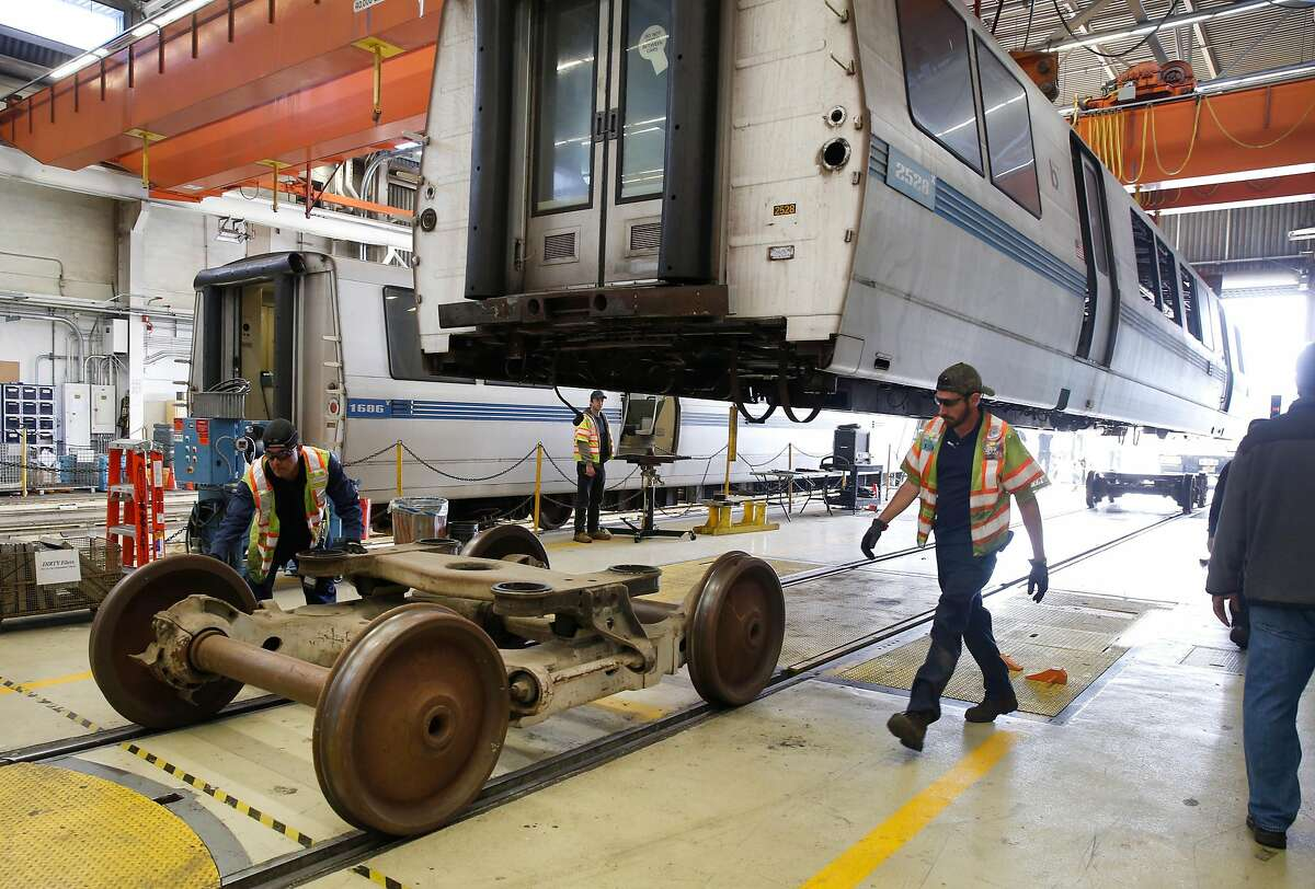 Maintenance workers roll temporary wheels away from a retired BART car before it is lowered onto a flatbed truck at the BART maintenance yard in Hayward, Calif. for transfer to a scrapyard on Friday, Nov. 8, 2019. Placed into service in 1995 and after logging more than 2.2 million miles, car number 2528 is the first of the transit agency's fleet of the past to be scrapped now that 58 of the