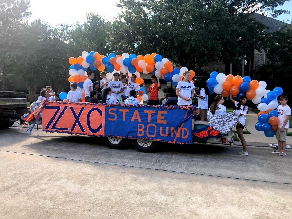 The Seven Lakes High School cross-country team rides their float during the 2019 homecoming parade.