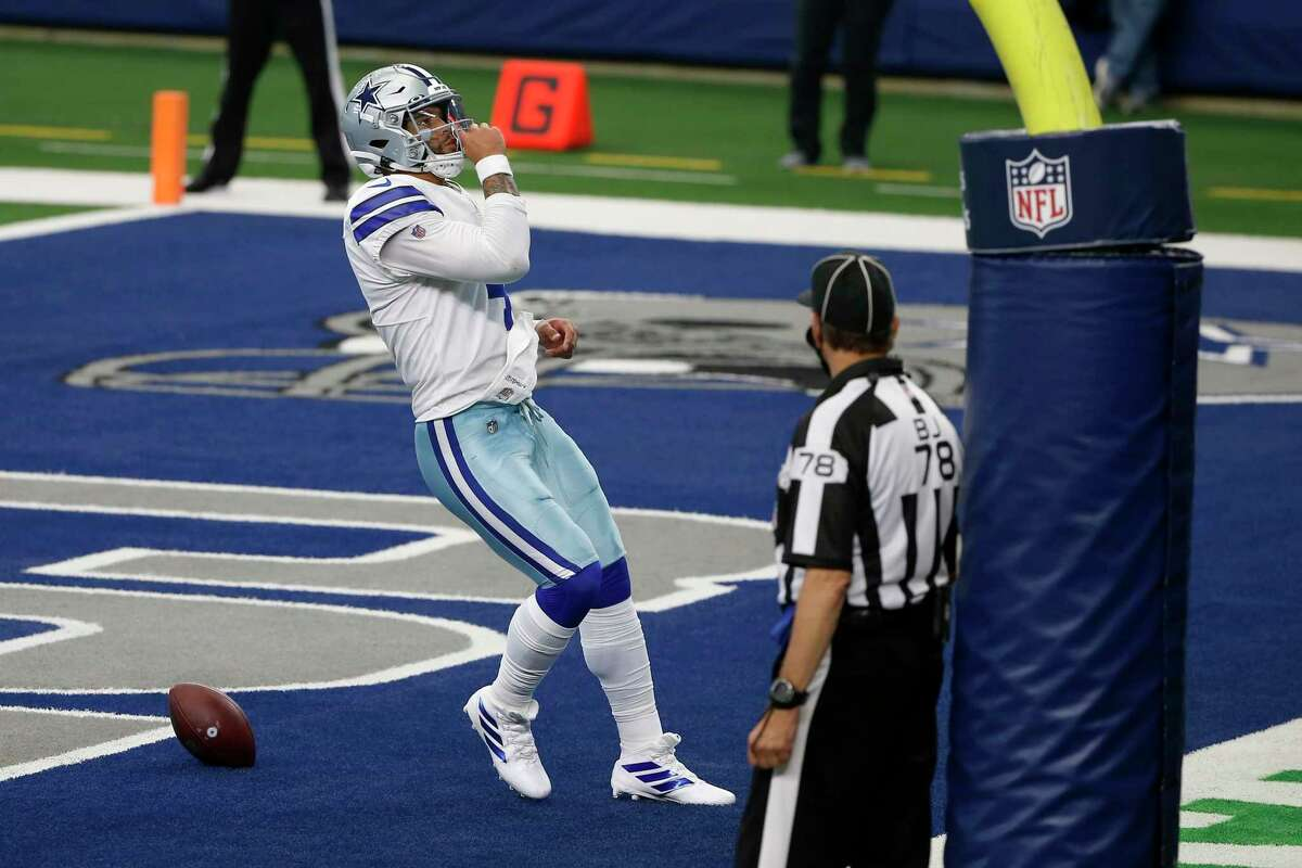 Dallas Cowboys quarterback Dak Prescott (4) celebrates running the ball for a touchdown as back judge Greg Meyer (78) looks on in the second half of an NFL football game against the Atlanta Falcons in Arlington, Texas, Sunday, Sept. 20, 2020.
