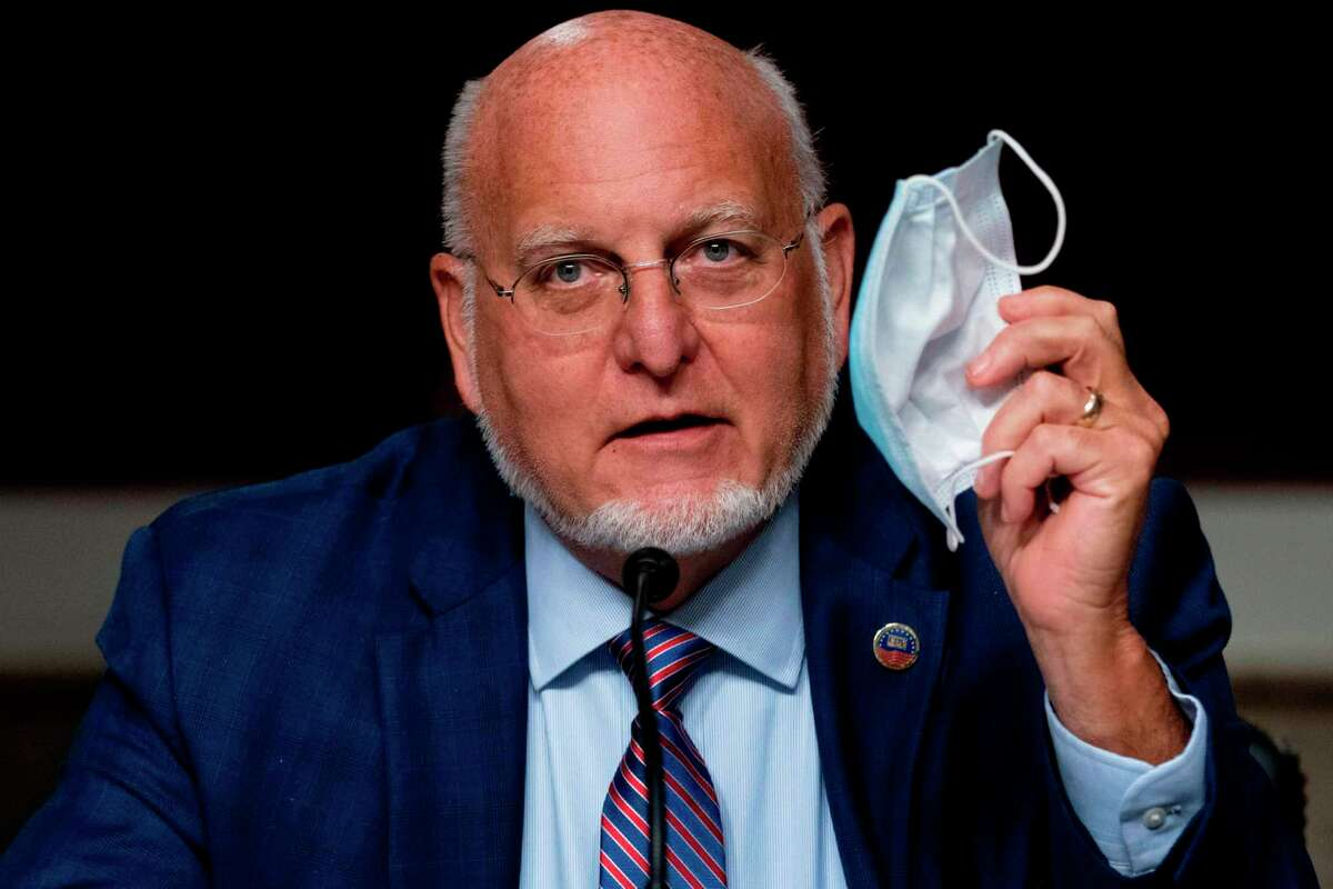 Centers for Disease Control and Prevention Director Dr. Robert Redfield holds up his mask during a recent Senate hearing. Messaging out of the CDC has been wildly inconsistent.