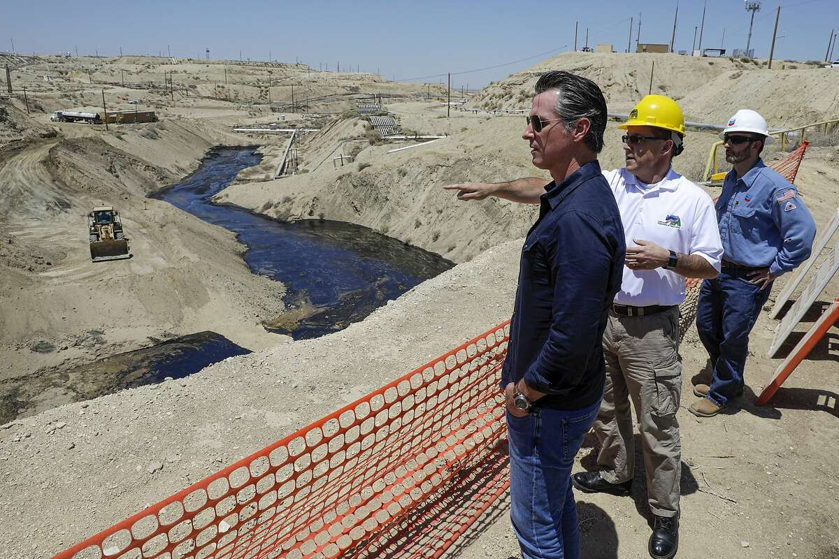 FILE - In this July 24, 2019, file photo, Gov. Gavin Newsom, left, is briefed by Jason Marshall, of the California Department of Conservation, Division of Oil and Gas, center; Billy Lacobie, of Chevron, while touring the Chevron oil field in McKittrick, Calif. Newsom says he is encouraged by Chevron's efforts to clean up what has turned into the state's largest oil spill in decades. California Gov. Newsom moved Wednesday, Sept. 23, 2020 to end issuing new hydraulic fracturing permits by 2024, a delay criticized by many environmental groups but characterized as legally and politically realistic by another. (Irfan Khan/Los Angeles Times via AP, Pool, File)