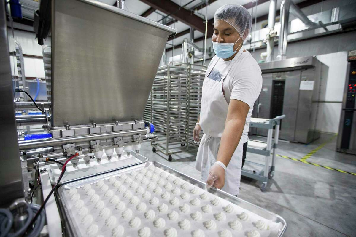 Felipe Flores waits for a sheet of meringues to roll off the depositor at Santte Foods Thursday, Sept. 24, 2020 in Oak Ridge North. Business is picking up for Santte Foods after several slow months when COVID-19 hit. The manufacturer of Tidbits Fun Bites reached a deal with Sam's Club to sell the low calorie meringue treats at select Houston stores on a trial basis.The facility currently produces between 50,000 and 65,000 bags per month of two-calorie meringue cookies. They are gluten free, lactose free, soy free and non GMO and use all natural ingredients. There are also product lines for diabetics and those following a keto diet.