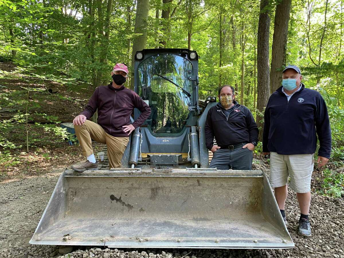 Earth movers quit for a few minutes at the Bristow Bird Sanctuary and Wildwood Preserve in New Canaan, Conn. to observe the revitalization groundbreaking for the 16.8-acre park on Tuesday, September 22, 2020. In the bulldozer lift, from left to right is: Conservation Commission Chairman Chris Schipper; Director of DPW Tiger Mann; and Superintendent of Parks John Howe.