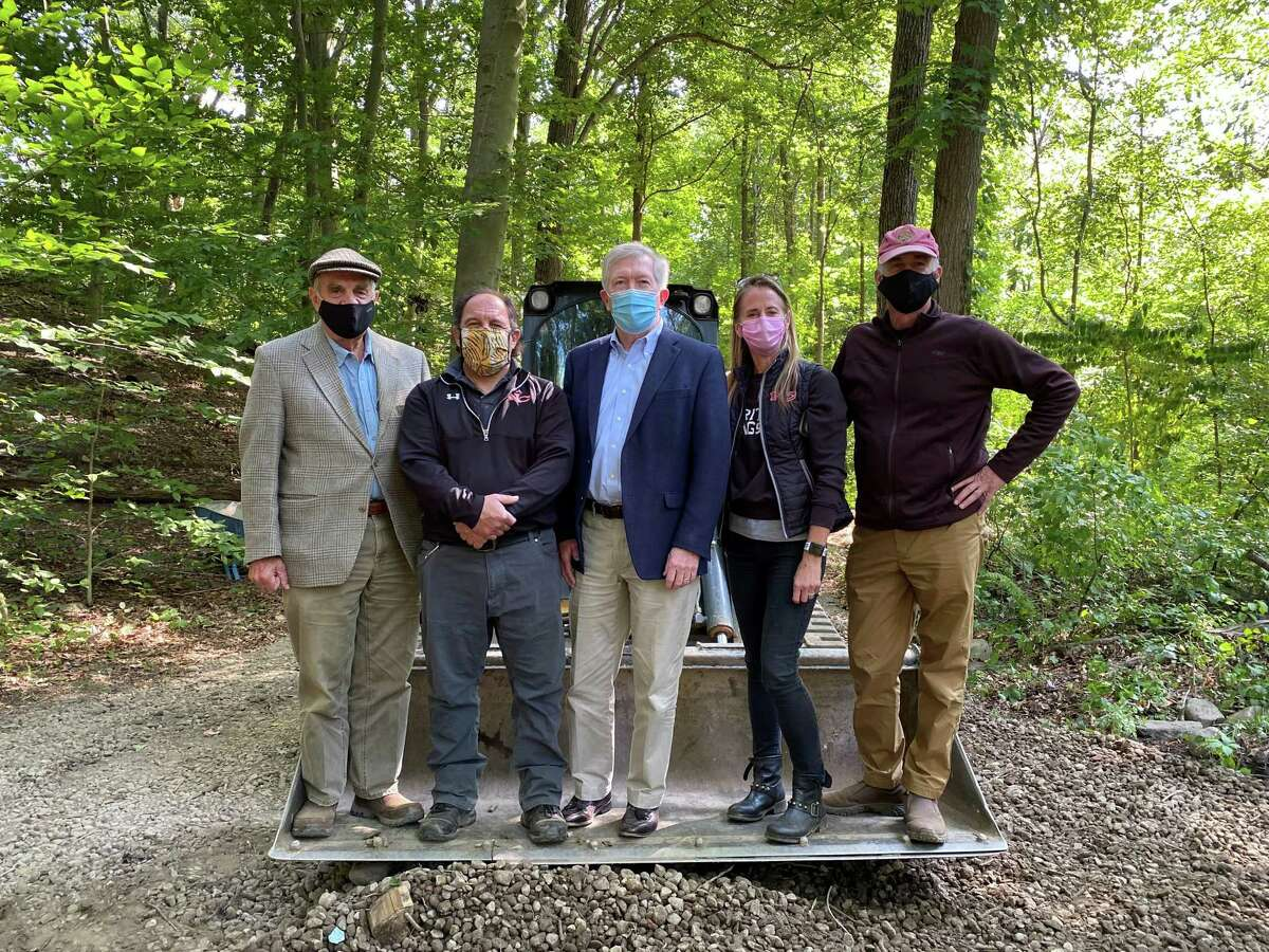 A group of town officials and town employees met at the crossroads at the Bristow Bird Sanctuary and Wildwood Preserve in New Canaan, Conn. to observe the revitalization groundbreaking for the 16.8-acre nationally renowned park on Tuesday, September 22, 2020. Standing on the bulldozer were: Landscape architect Keith Simpson; Director of DPW Tiger Mann; First Selectman Kevin Moynihan; Chairman of the Parks and Recreation Commission Rona Siegel; and Conservation Commission Chairman Chris Schipper.