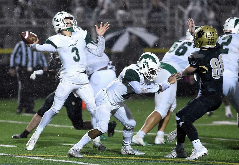 Maloney quarterback Angel Arce passes against Hand in the Class L semifinals in Madison in December. Photo: Arnold Gold / Hearst Connecticut Media / New Haven Register