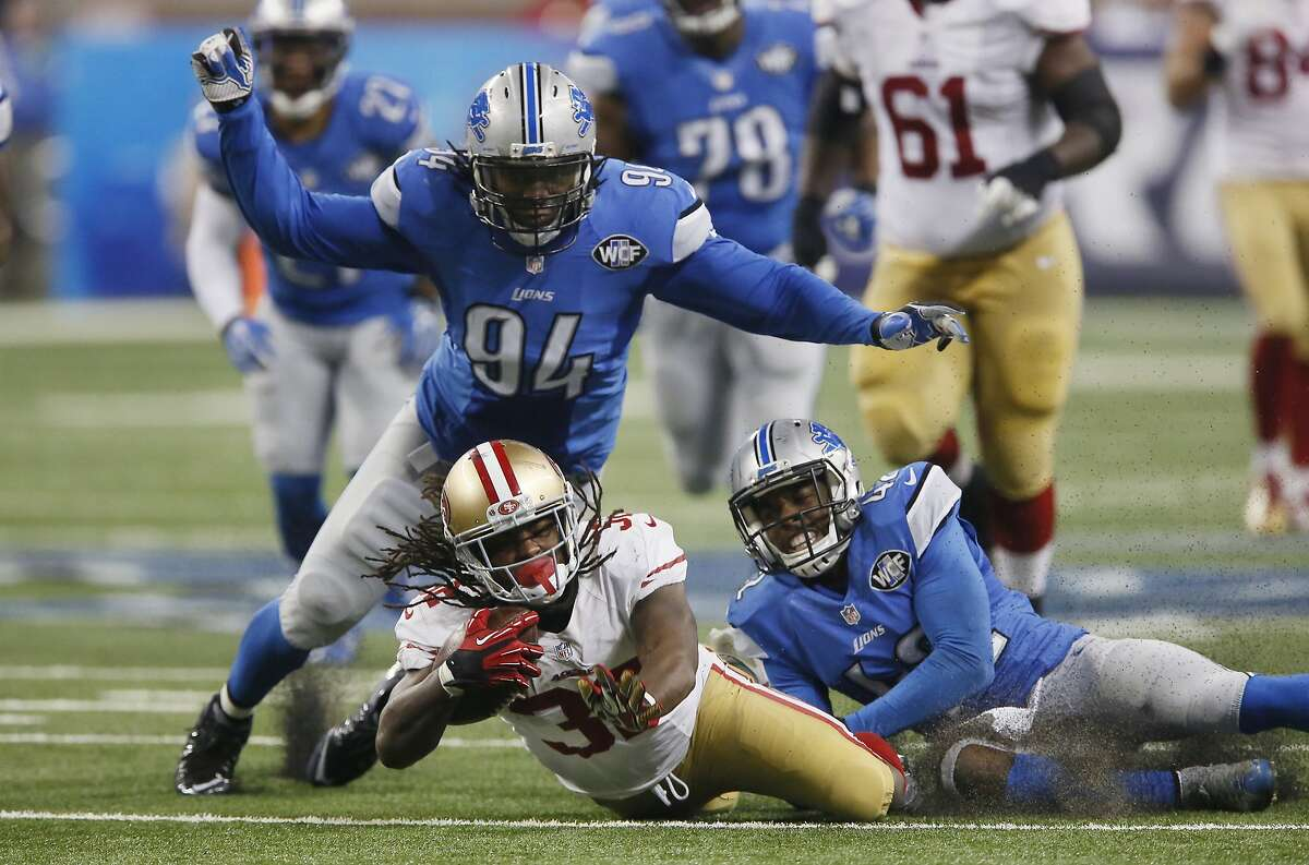 """Ezekiel """"Ziggy"""" Ansah (94), shown here jumping on 49ers running back DuJuan Harris in a 2015 game, spent six seasons with the Detroit Lions."""