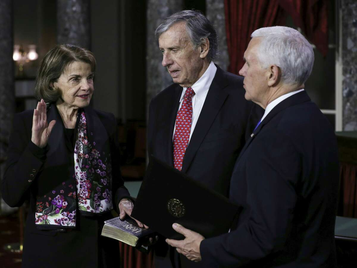 US Senator from California Dianne Feistein (L) flanked by her husband Richard Blum is sworn in by Vice President Mike Pence (R) during the swearing-in re-enactments for elected senators in the Old Senate Chamber on Capitol Hill January 3, 2019.
