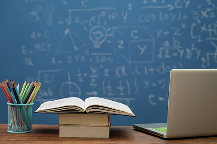 Back to school supplies. Books and blackboard on wooden background Photo: Seksan Mongkhonkhamsao | Getty Images