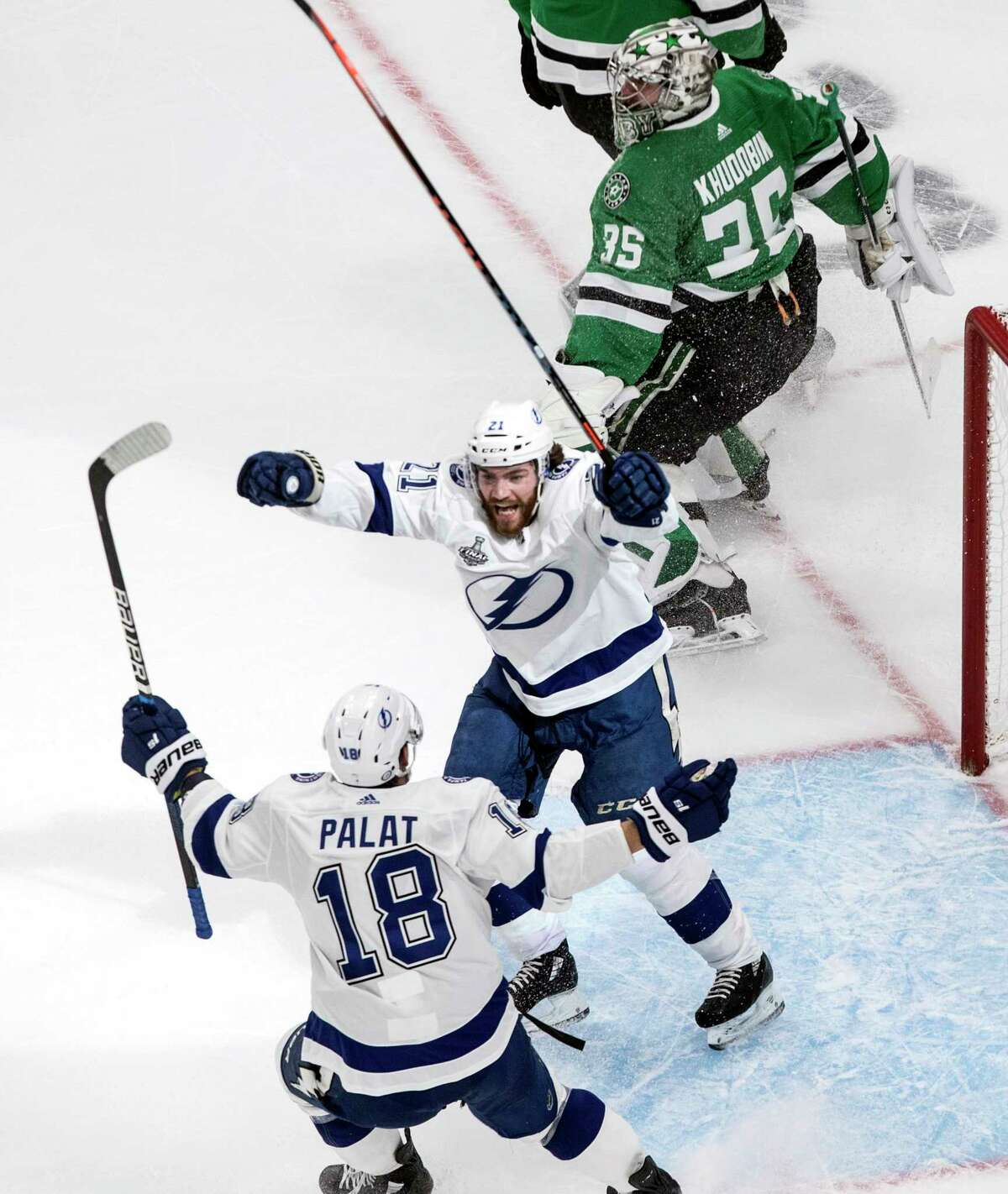 Tampa Bay Lightning center Brayden Point (21) celebrates his goal past Dallas Stars goaltender Anton Khudobin (35) with with teammate Ondrej Palat (18) during the second period of Game 3 of the NHL hockey Stanley Cup Final, Wednesday, Sept. 23, 2020, in Edmonton, Alberta. (Jason Franson/The Canadian Press via AP)