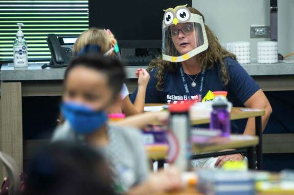 Principal Euberta Lucas kneels down to talk to a student on the first day of in-person classes at McElwain Elementary School on Tuesday, Sept. 8, 2020 in Katy.