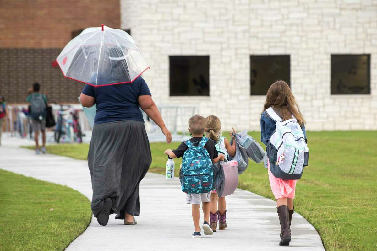 Assistant principal Miranda Cummings walks with students up the sidewalk for their first day of in-person classes at McElwain Elementary School on Tuesday, Sept. 8, 2020 in Katy. A little less than half of Katy ISD's students returned to their classrooms for in-person instruction this week. The remainder of the districts students will to to school remotely, due to coronavirus precautions.