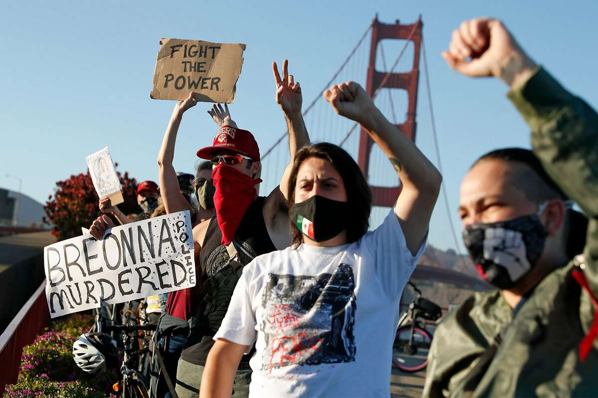 A small group of protesters demonstrate on the south end of the Golden Gate Bridge on Thursday over the lack of charges in the shooting death of Breonna Taylor.