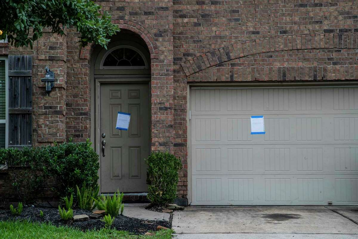 Eviction notice taped on the garage door and front door of a property intended for Carroll Shelton Richardson from his landlord Thursday, Sept. 24, 2020, in Houston.