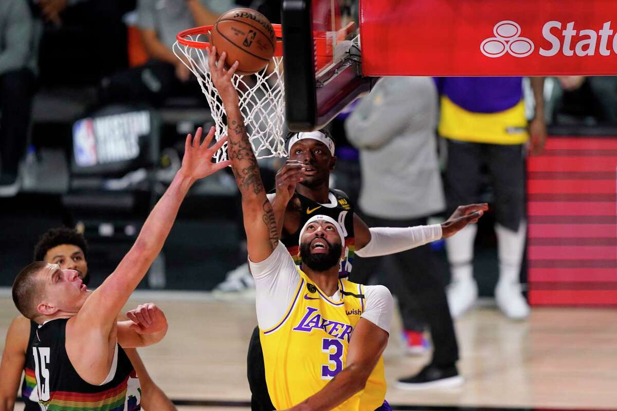 Los Angeles Lakers' Anthony Davis (3) shoots against Denver Nuggets' Nikola Jokic (15) during the first half of an NBA conference final playoff basketball game Thursday, Sept. 24, 2020, in Lake Buena Vista, Fla. (AP Photo/Mark J. Terrill)