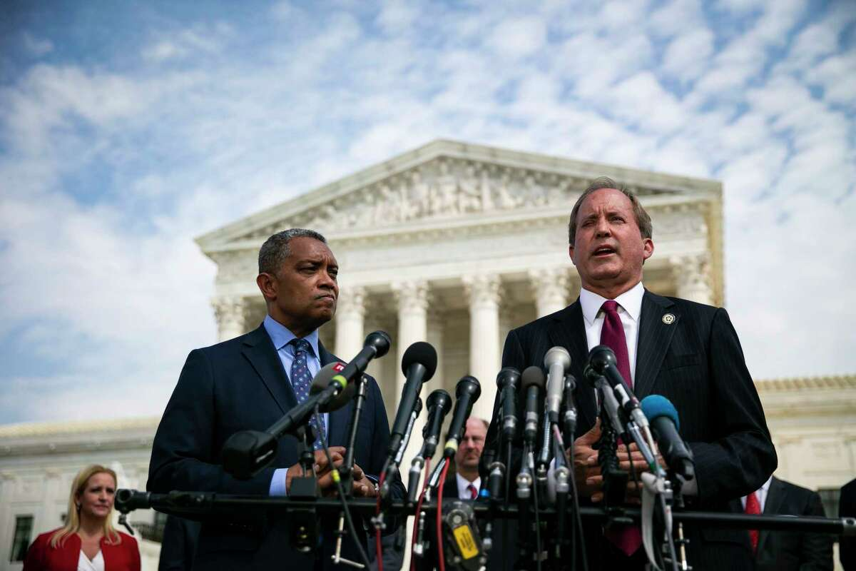 FILE -- Ken Paxton, attorney general of Texas, right, and Karl Racine, attorney general of the District of Columbia, speak about the investigation into Google during a news conference outside of the Supreme Court in Washington, Sept. 9, 2019. (Al Drago/The New York Times)