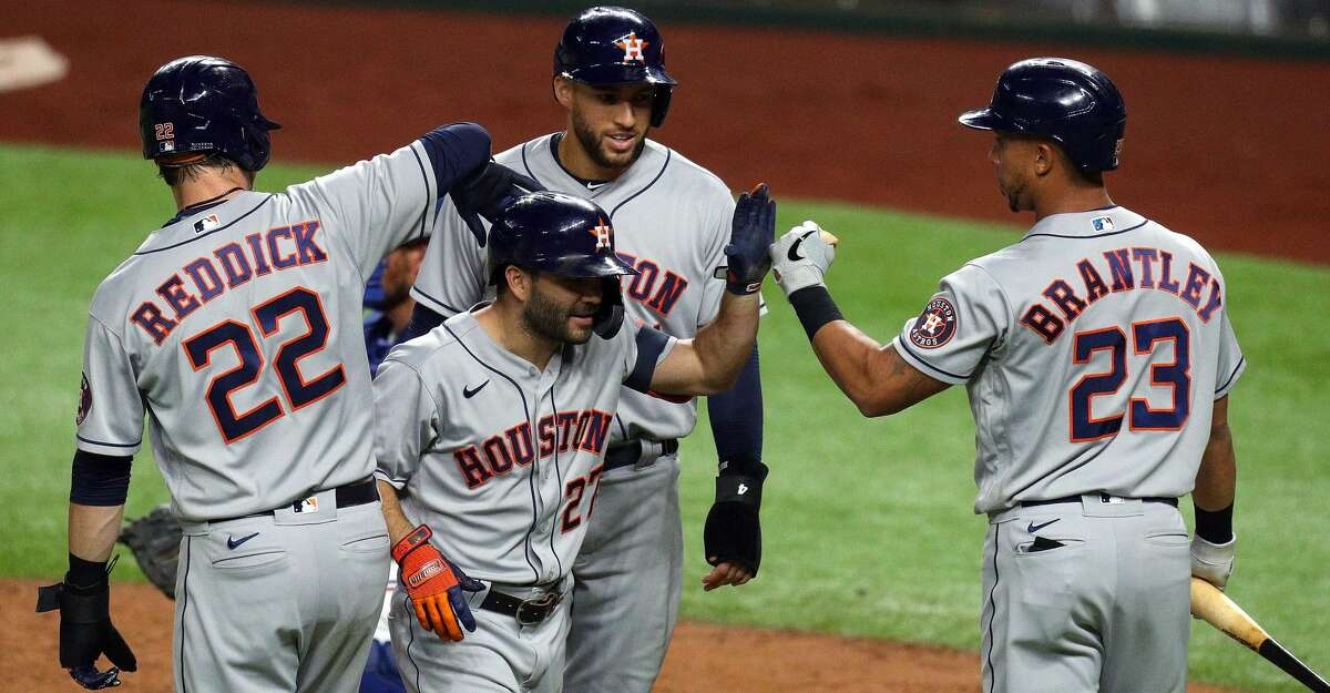 Jose Altuve #27 of the Houston Astros is greeted at the plate by Josh Reddick #22, George Springer #4, and Michael Brantley #23 after a three-run homer run against the Texas Rangers in the sixth inning at Globe Life Field on September 24, 2020 in Arlington, Texas. (Photo by Richard Rodriguez/Getty Images)