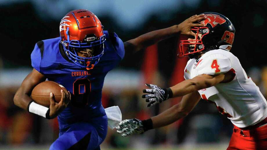 Grand Oaks quarterback James Holmon (9) stiff-arms Caney Creek defensive back Marcelino Zuniga (4) during the first quarter of a non-district high school football game at Woodforest Bank Stadium, Thursday, Sept. 24, 2020, in Shenandoah. Photo: Jason Fochtman, Houston Chronicle / Staff Photographer / 2020 © Houston Chronicle