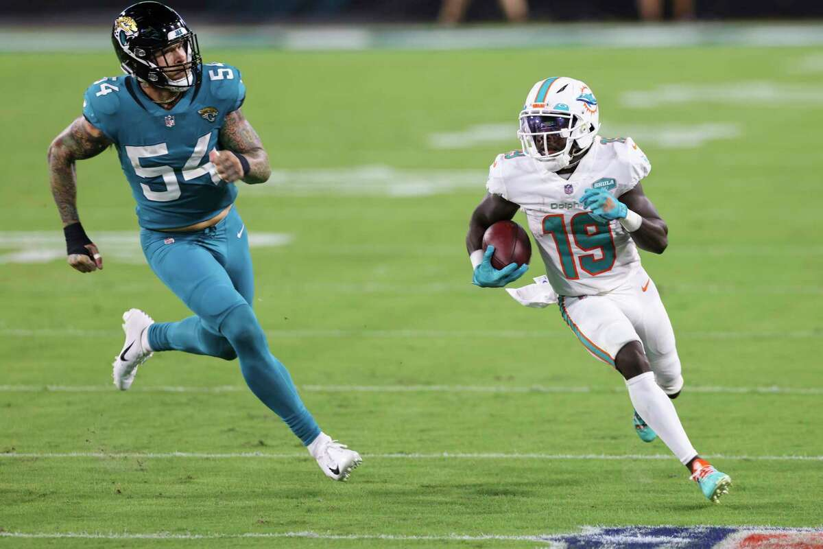 JACKSONVILLE, FLORIDA - SEPTEMBER 24: Jakeem Grant #19 of the Miami Dolphins runs for yardage against Cassius Marsh #54 of the Jacksonville Jaguars during the first quarter of a game at TIAA Bank Field on September 24, 2020 in Jacksonville, Florida. (Photo by James Gilbert/Getty Images)