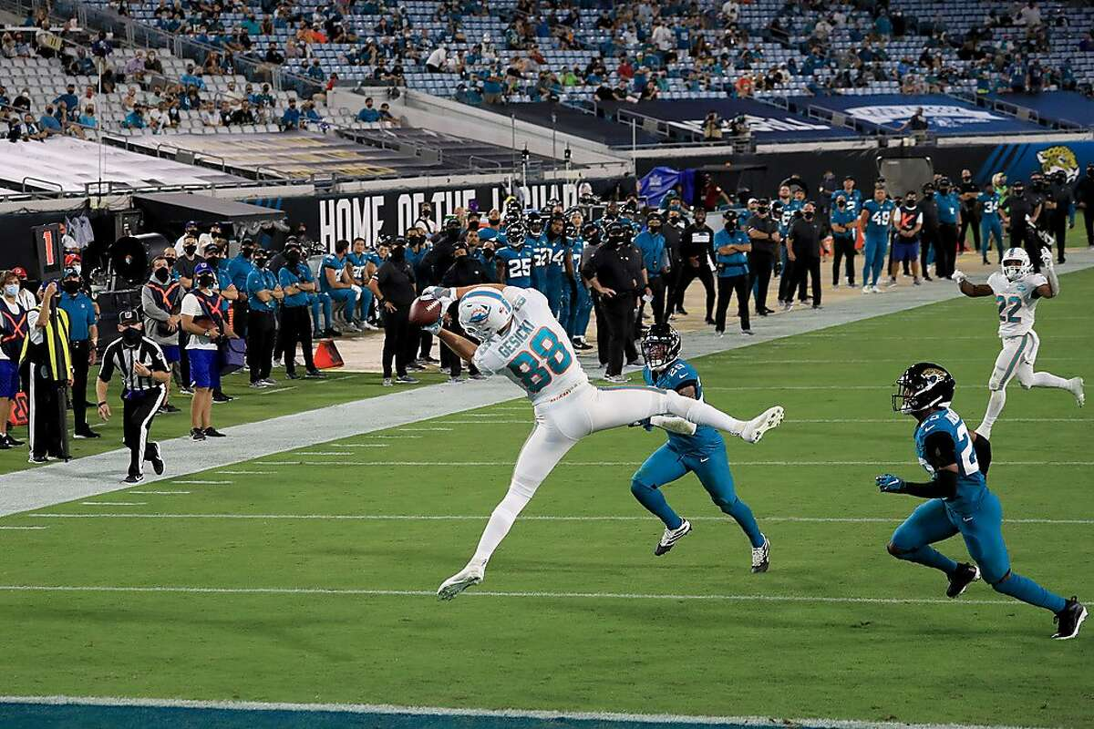 Miami's Mike Gesicki contorts his body for a touchdown reception from quarterback Ryan Fitzpatrick (not pictured) against the Jaguars in Jacksonville, Fla., on Thursday night.