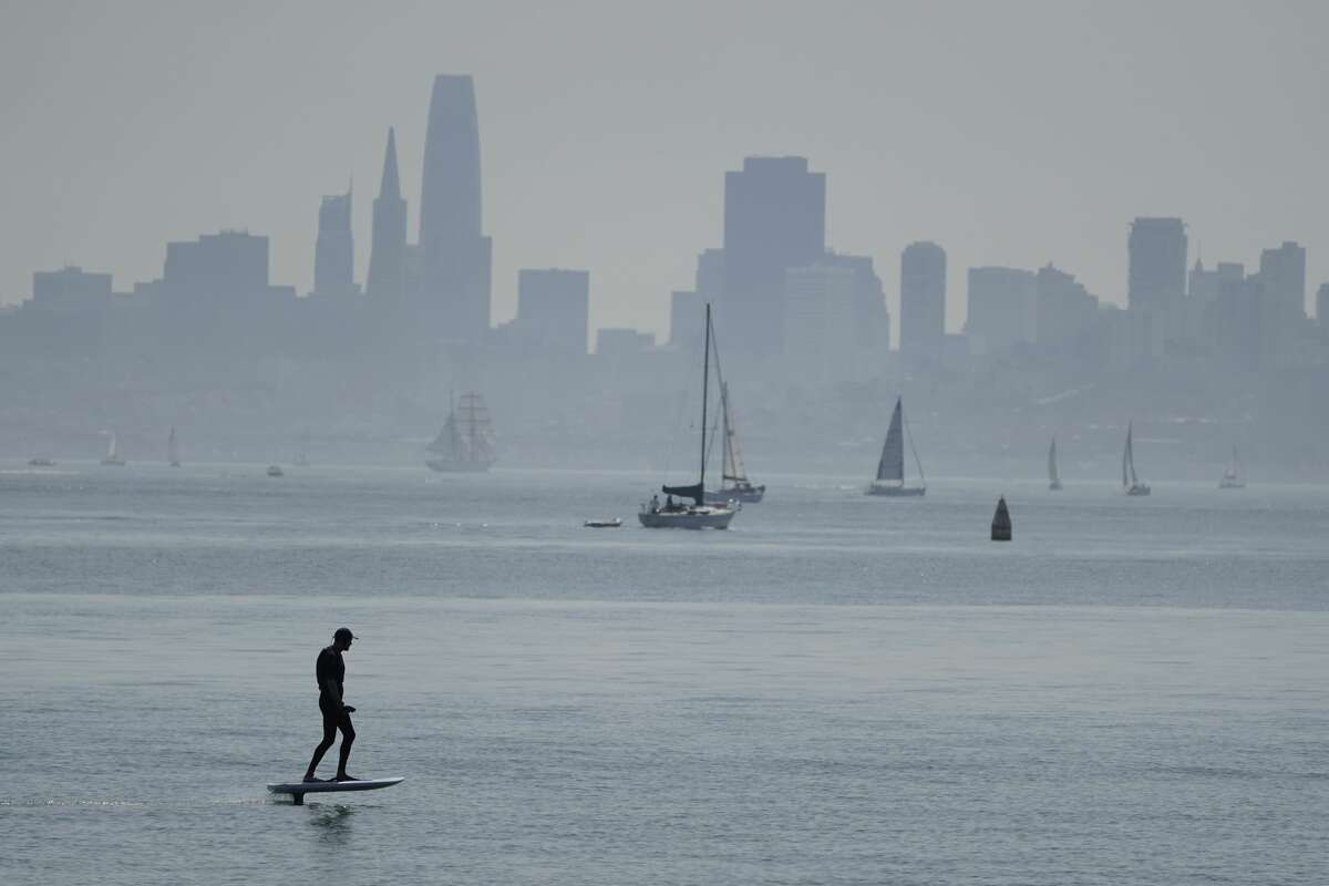 A man rides a powered surfboard on the bay with the San Francisco skyline in the background Saturday, Sept. 5, 2020, in Sausalito, Calif. California is sweltering under a heat wave as offshore winds increase the risk of fire danger.