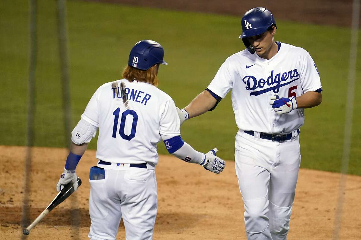 Los Angeles Dodgers' Corey Seager, right, celebrates his solo home run with Justin Turner during the third inning of the team's baseball game against the Oakland Athletics on Thursday, Sept. 24, 2020, in Los Angeles. (AP Photo/Marcio Jose Sanchez)