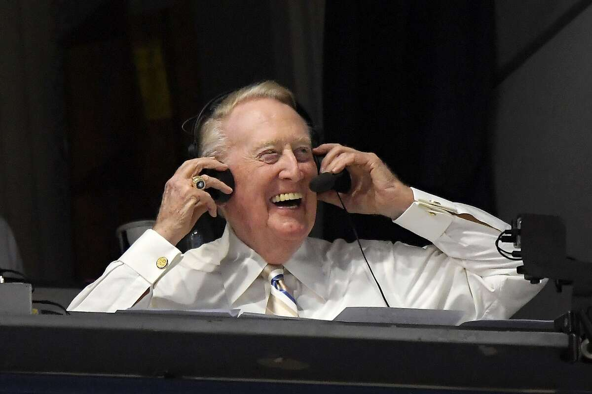 FILE - In this Sept. 19, 2016, file photo, Los Angeles Dodgers Hall of Fame announcer Vin Scully puts his headset on prior to a baseball game between the Dodgers and the San Francisco Giants in Los Angeles. Items from the personal collection of the Hall of Fame broadcaster sold at auction for over $2 million after online bidding ended Wednesday, Sept. 23, 2020. (AP Photo/Mark J. Terrill, File)