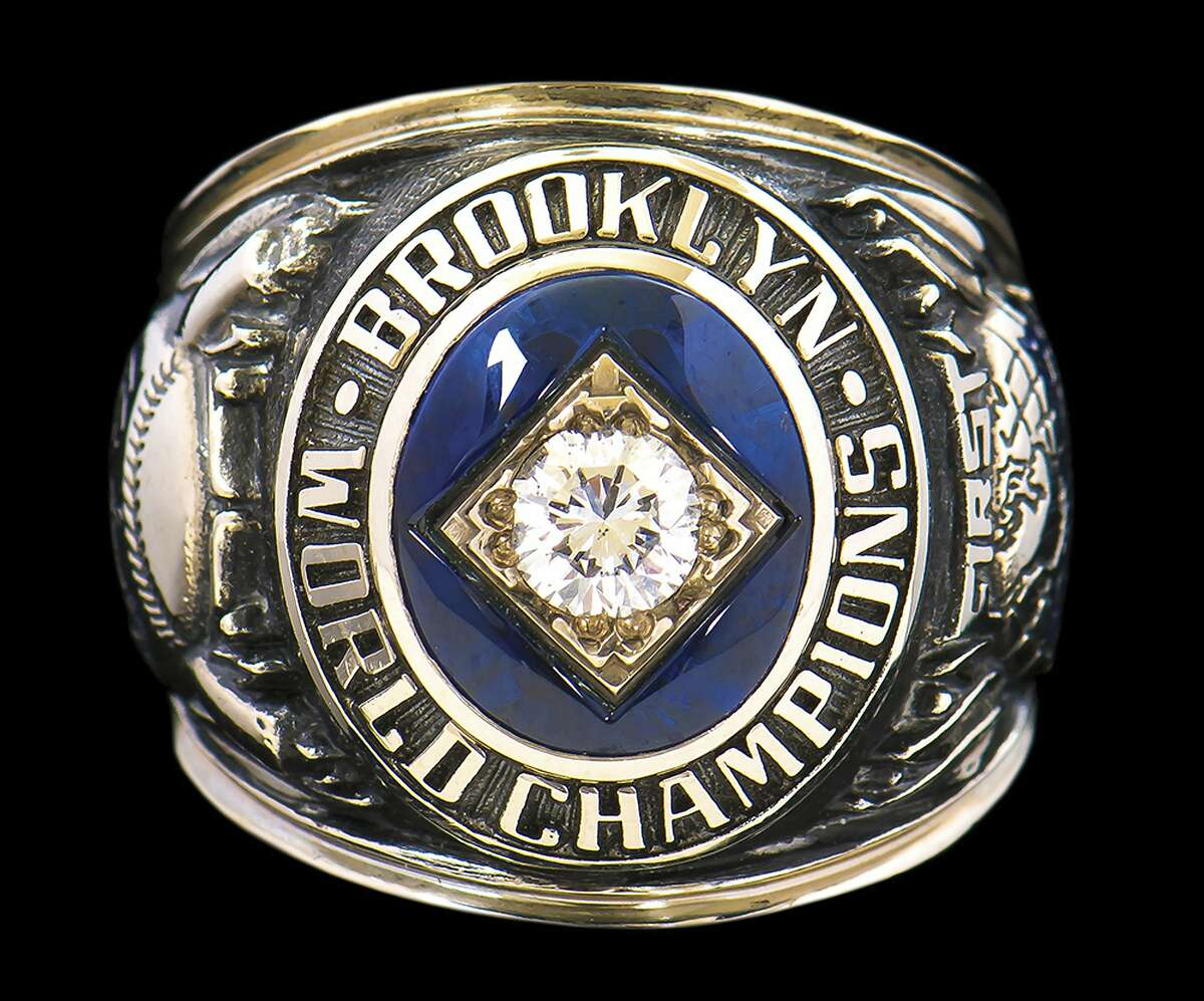 FILE- This photo released by Hunt Auctions shows broadcaster Vin Scully's the 1955 Brooklyn Dodgers World Series Championship ring. Items from the personal collection of the Hall of Fame broadcaster sold at auction for over $2 million after online bidding ended Wednesday, Sept. 23, 2020. The A Brooklyn Dodgers ring presented to Scully in the 1950s sold for $184,475. (Hunt Auctions via AP, File)