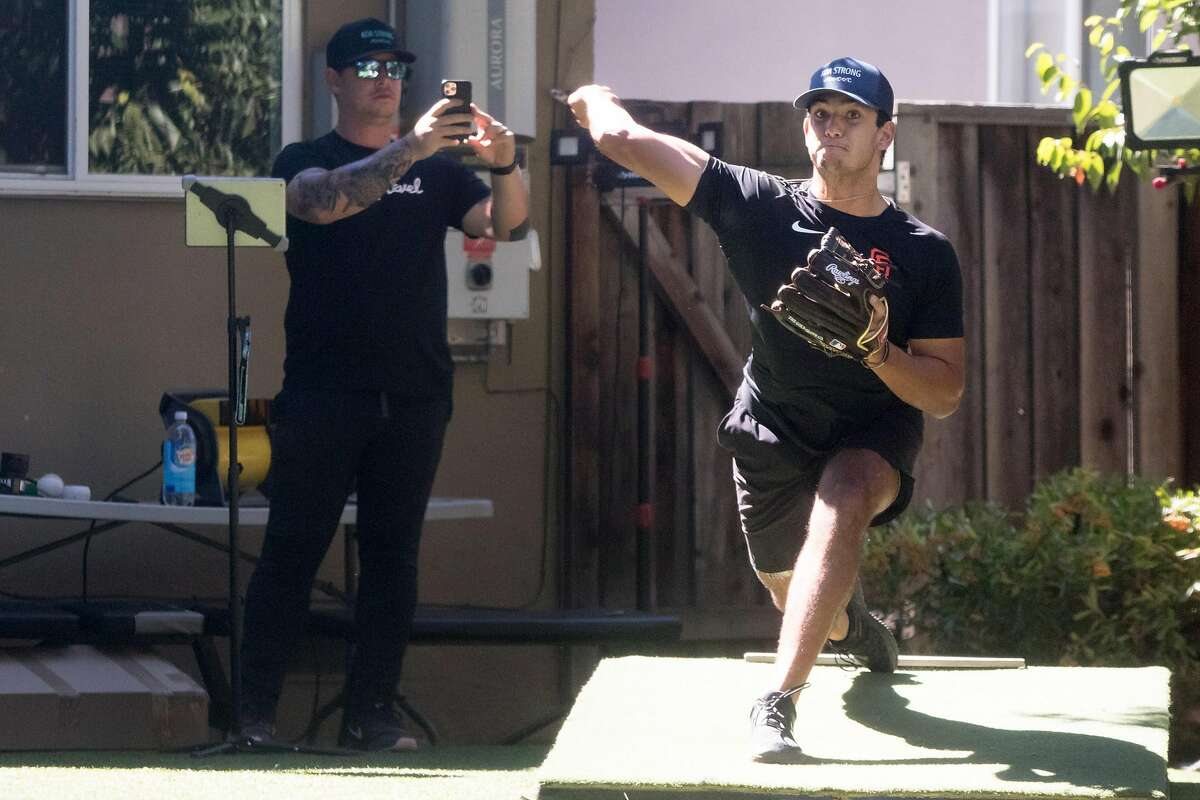 San Francisco Giants minor league pitcher Kanoa Pagán throws a session while his pitching coach Nick Sanzeri looks on in Campbell, Calif., on September 22, 2020.