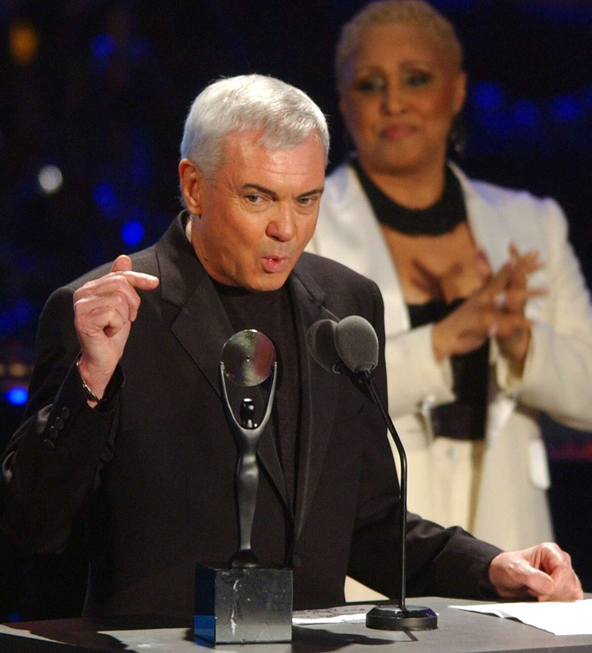 Gene Pitney points to his award while being inducted into the Rock and Roll Hall of Fame during the induction ceremony as Darlene Love looks on Monday, March 18, 2002, at New York's Waldorf Astoria.