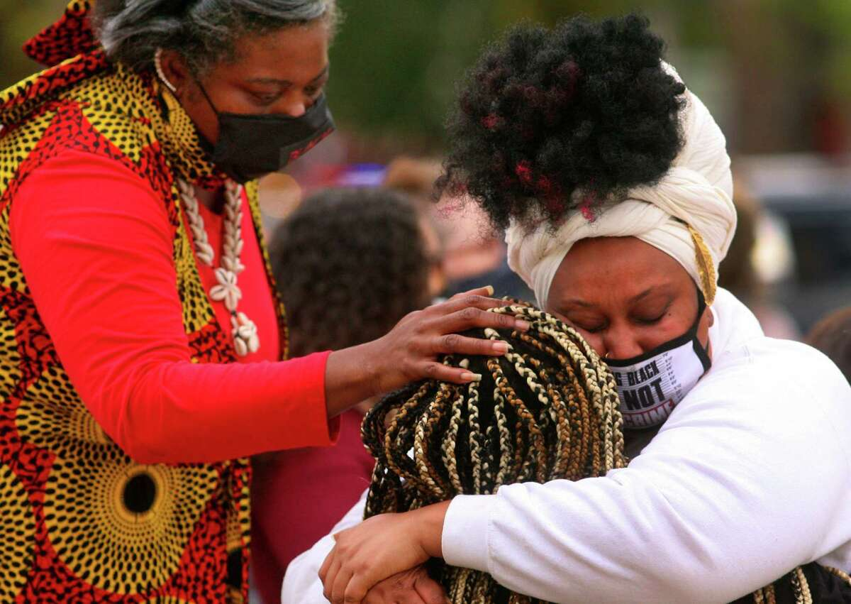 Attallah Sheppard, with Artivism, receives and hug from Black Lives Matter New Haven organizer Sun Queen, facing camera, after Sheppard performed her spoken word piece entitled