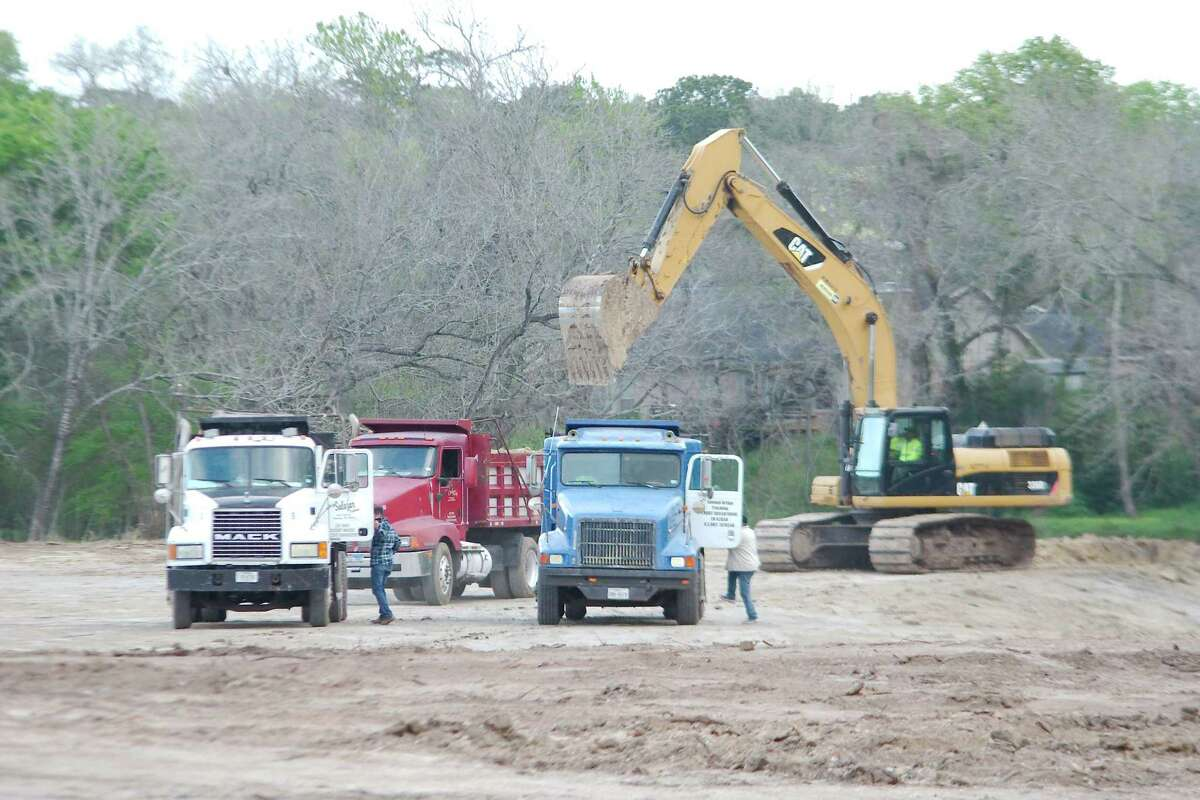 Dump trucks wait for loads earlier this year at the site of the flood control project at 1776 Memorial Park in Friendswood.