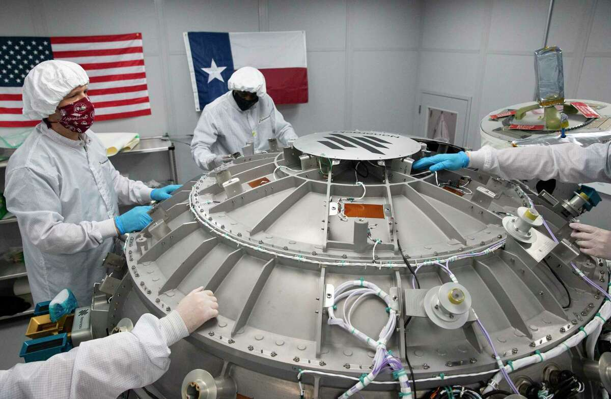 Nanoracks Director of Engineering Steven Stenzel, left, and Mechanical Lead Technician Hulon Polk work on installing the top protective panel to cover electronics and other parts of the Bishop Airlock Friday, Sept. 18, 2020, in Webster. The airlock will be shipped to Florida, where it will be launched to the International Space Station in November. It will ultimately increase the number and size of satellites, equipment and experiments that can access space from the station.