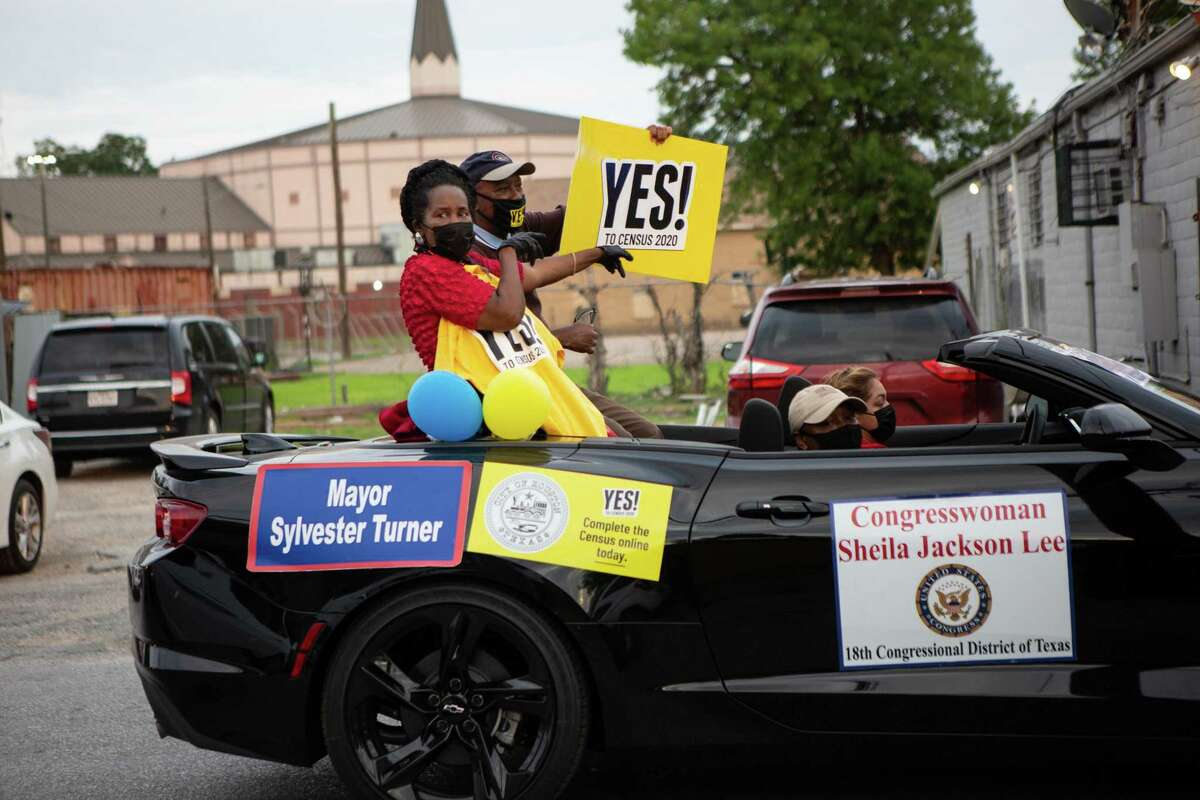 """Representative Sheila Jackson Lee and Mayor Sylvester Turner raise a """"Yes to Census 2020"""" sign as they cruise through Third Ward in the Census Bureau vehicle parade on Sept. 19, 2020."""
